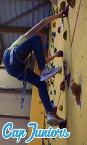 Un enfant en séance d'escalade sur un mur intérieur