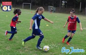 Une adolescente de 14 ans en pleine action de dribble sur un terrain de foot